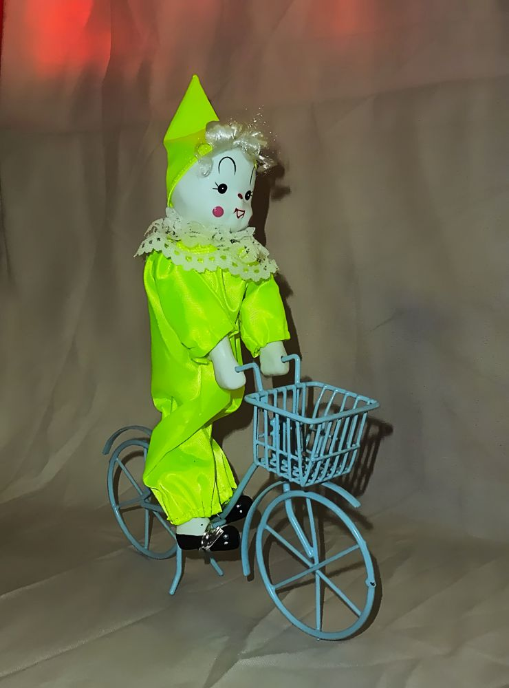 Pierrot in grünem Kostüm auf Fahrrad